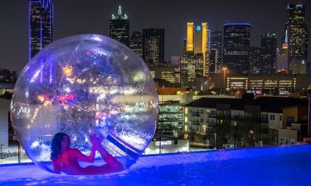 Girl in pool overlooking Dallas skyline