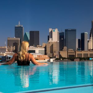 Woman in pool with Dallas Skyline