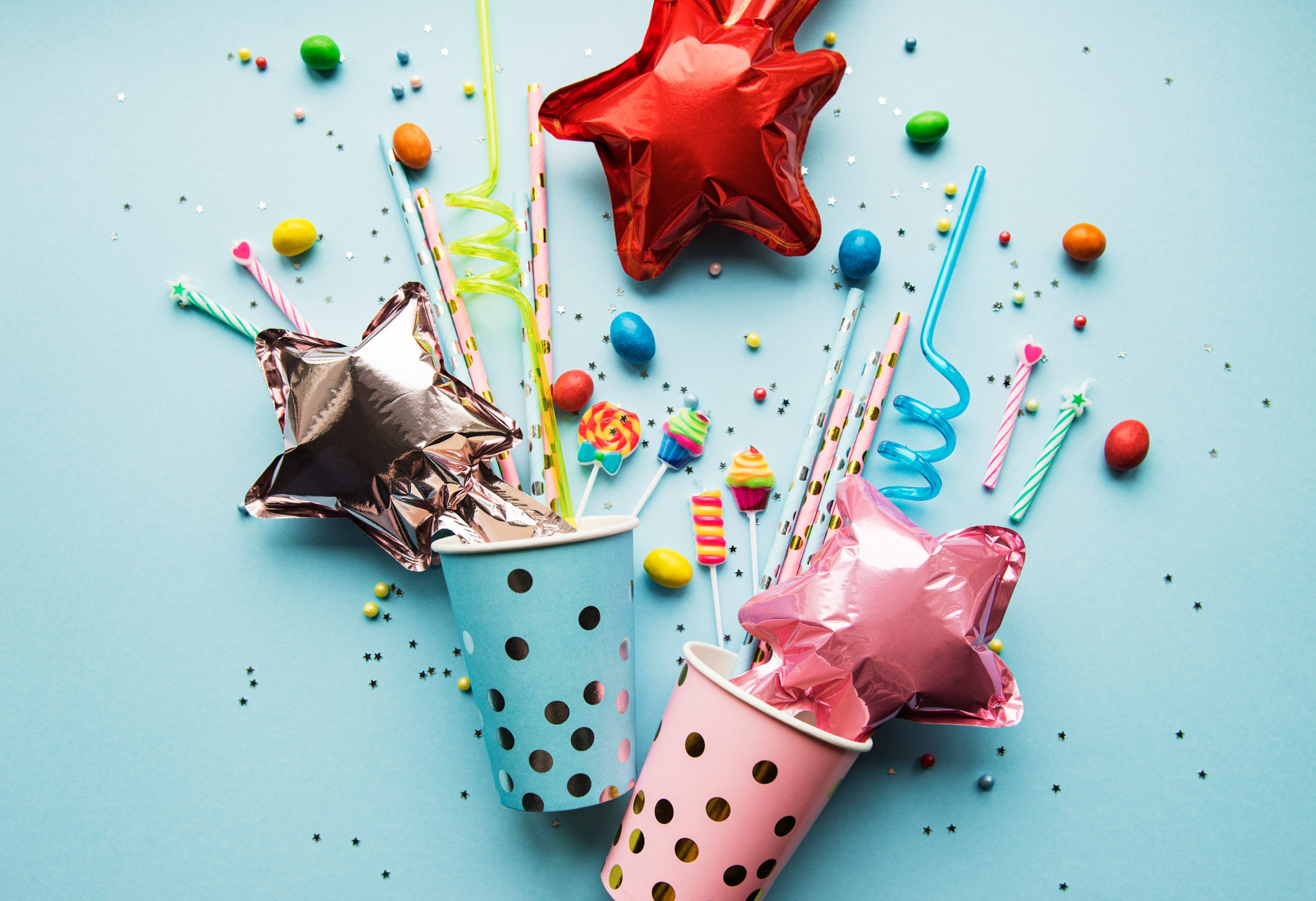 Birthday cups and balloons on blue background